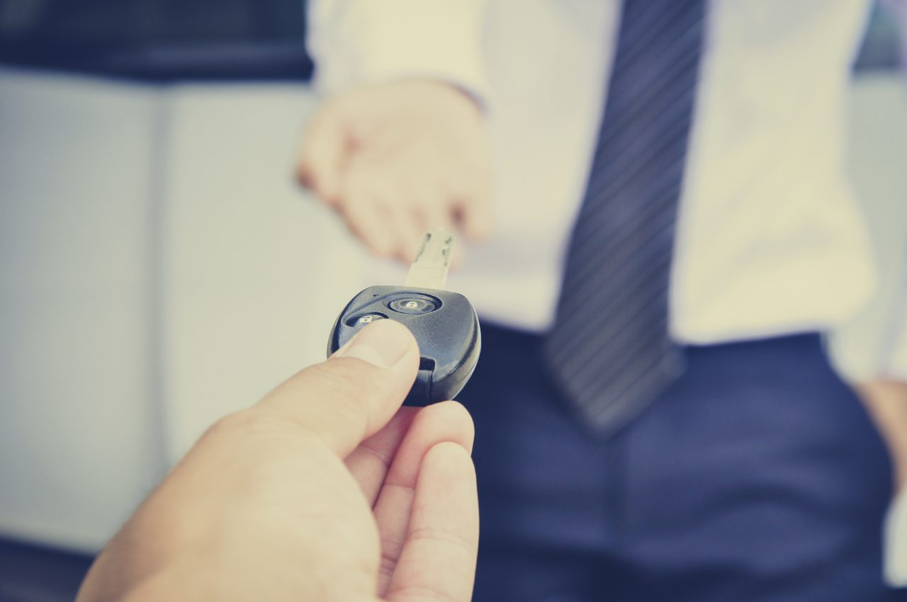 Hand giving car key to a businessman, car sale & rental concepts